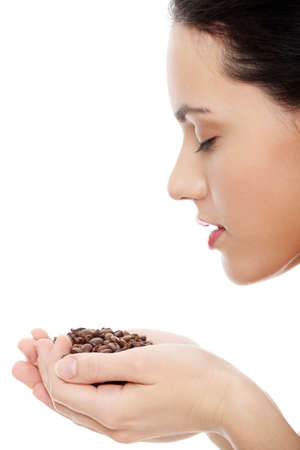 nose: Young woman holding asnd smelling coffee beans isolated on white