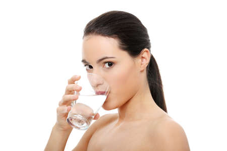 girl drinking water: Beautiful young woman drinks clear mineral water from glass. Isolated on white  Stock Photo