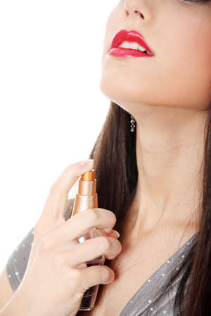 Beautiful woman applying perfume on her body, bright red perfume bottle  photo