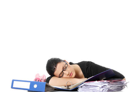 filling out: Exhausted female filling out tax forms while sitting at her desk.  Isolated on white