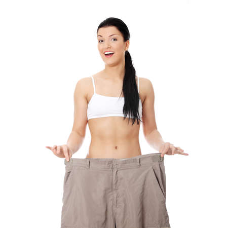 Young happy woman showing how much weight she lost. Isolated on white background photo
