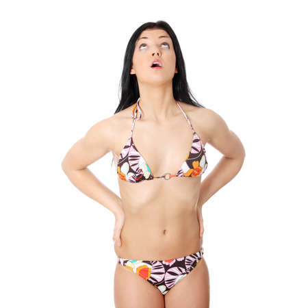 Summer young woman in bikini looking up, isolated on white background photo