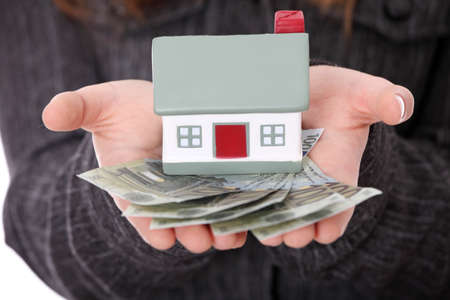 Beautiful young businesswoman holding euros bills and house model over white - real estate loan concept Stock Photo - 9035661