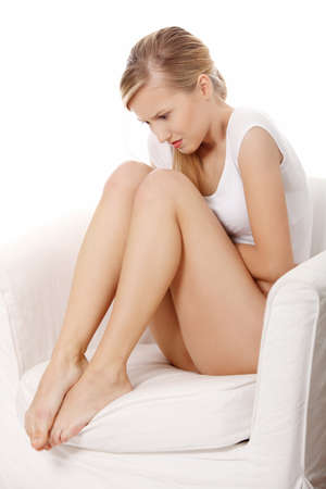 per�odo: Young blond woman with stomach issues sitting.