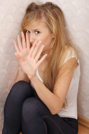 abused girl: Abused young woman trying to hide and defend herself  Stock Photo