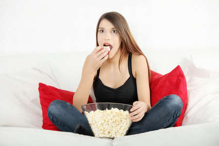 Beautiful young woman watching TV and eating popcorn photo