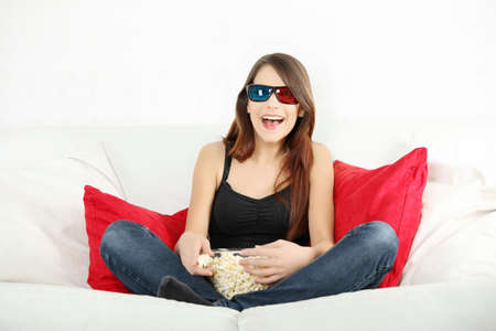 Beautiful young woman watching TV in 3d glasses and eating popcorn Stock Photo - 9035140