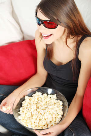 Beautiful young woman watching TV in 3d glasses and eating popcorn photo