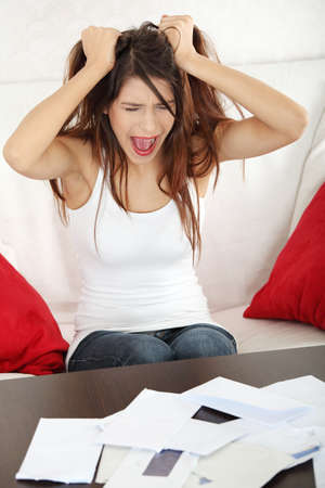 pay bills: A young beautiful woman stressed because of bills.  Stock Photo