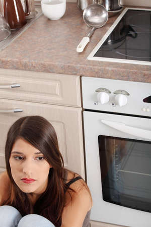 Depressed young woman sitting in kitchen Stock Photo - 9035946