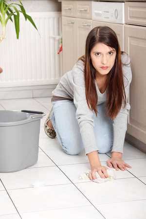 Young woman cleaning floor on her knees photo