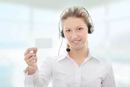 Call center woman with headset showing business card. Beautiful smiling caucasian woman photo