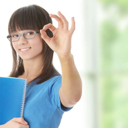 Teen student girl with note pad gesturing OK photo