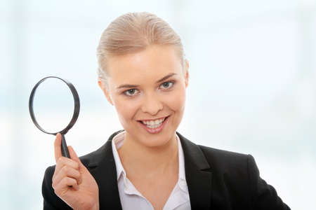 Young attractive smiling business woman looking into a magnifying glass photo