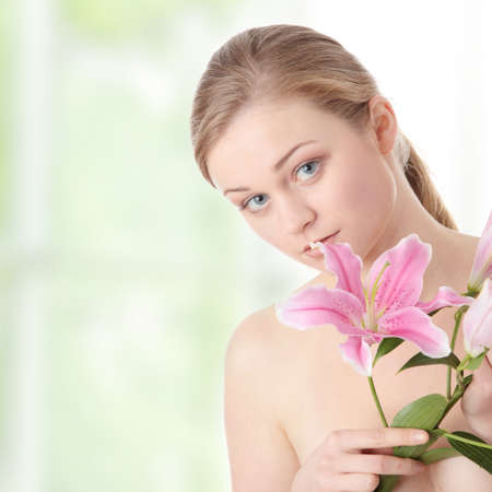 Portrait of young beautiful blond woman with lily flower