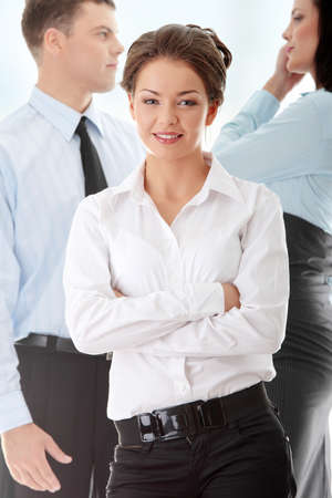 Businesswoman against two other businesspeople photo