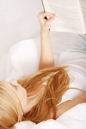 Beautiful young blond woman reading book on the bed at home  photo