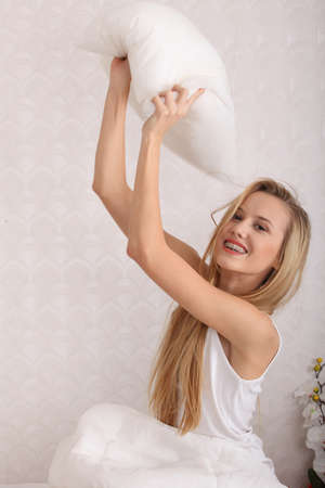 Young happy blond woman ready for pillow fight in the bed  photo