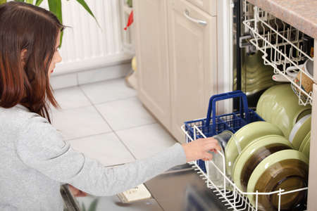 Young woman in kitchen doing housework. Puling out dishes from dishwasher photo
