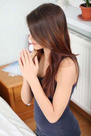 Young woman praying at home photo