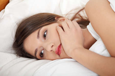 caras tristes: Linda joven tumbado en la cama. Pensamiento triste