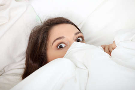 defenseless: Scared young woman in bed.