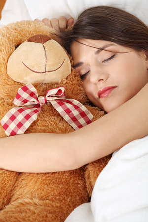 Charming brunette in bed with her teddy bear  photo