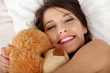 plush toy: Charming brunette in bed with her teddy bear