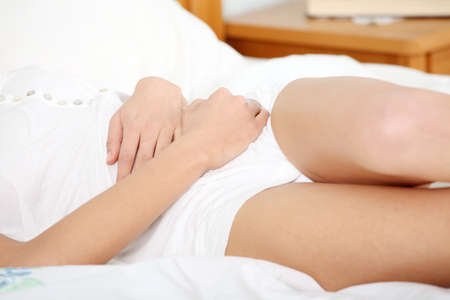 Young woman stroking her belly becouse of bellyache Stock Photo - 9034415