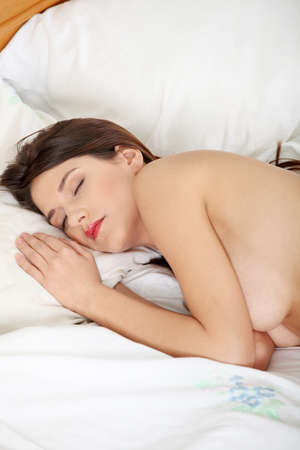 Closeup portrait of a cute young woman sleeping on bed  Stock Photo - 9034936