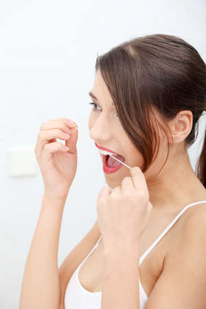 dental floss: Beautiful young woman using dental floss at bathroom