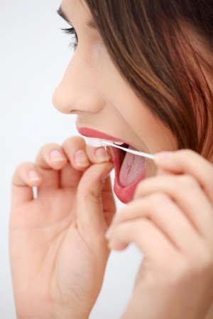 flossing: Beautiful young woman using dental floss at bathroom