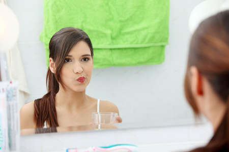 Young beautiful brunette woman using mouthwash at her bathroom