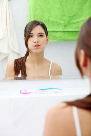 enjuague bucal: Joven y bella mujer Morena mediante enjuague bucal en su cuarto de ba�o