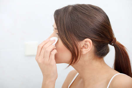 removing: Young beautiful caucasian woman cleaning her face with cotton pad in the bathroom
