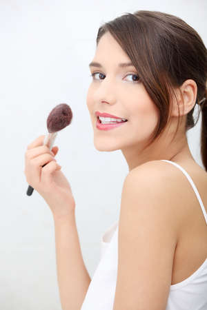 Portrait of attractive young adult woman applying blusher in her bathroom photo