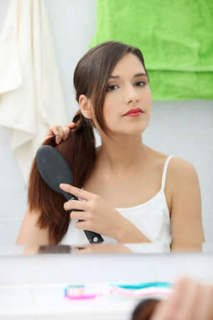 Beautiful young woman brushing her hair at bathroom photo