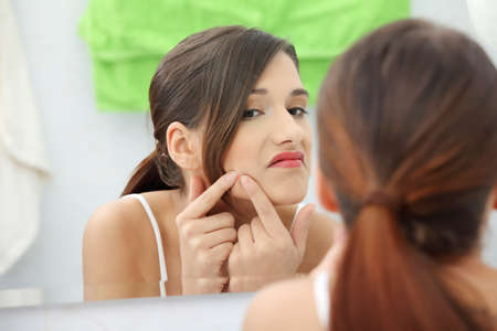 Young teenage woman with pimple on her face Stock Photo - 9035962