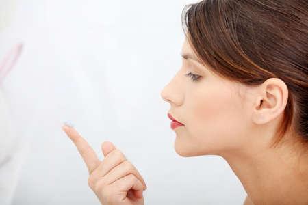 eye contact: Beautiful young caucasian woman putting a contact lens at bathroom