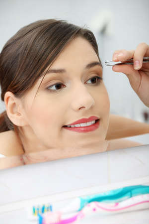 plucking: Young beautiful woman plucking her eyebrows with tweezers at her bathroom Stock Photo