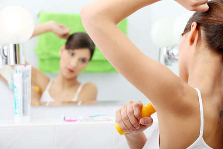 perspiration: Young beautiful caucasian woman using deodorant at her bathroom