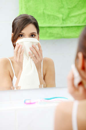 Beautiful woman wipes her face with a towel at bathroom  Stock Photo - 9034966