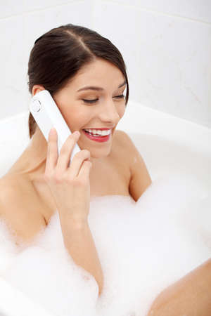 Beautiful young woman talking by wireless phone while taking a bath photo