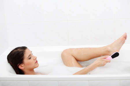 Woman in bath rubbing heel of foot with brush for a pedicure . Stock Photo - 9033200