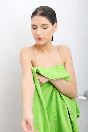 Beautiful woman wipes her wet body with a towel at bathroom photo
