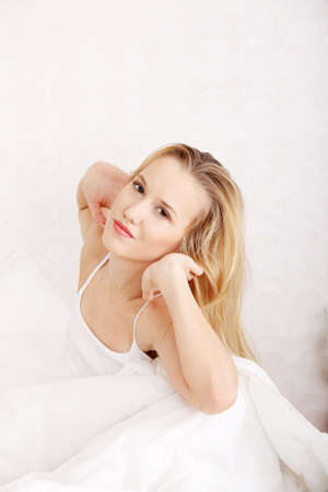 Happy young blond woman stretching in bed Stock Photo - 9248746