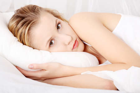 Sad young woman lying in bed Stock Photo - 9254040