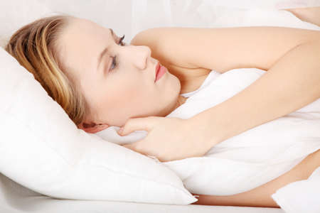 Sad young woman lying in bed Stock Photo - 9248755