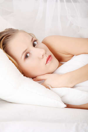 Sad young woman lying in bed Stock Photo - 9254116
