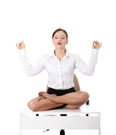 Beautiful businesswoman sitting on white desk in lotus flower position of yoga. Isolated on white  photo